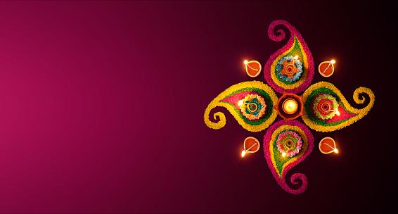 Diwali celebration - Diya oil lamps lit on colorful rangoli 995955630