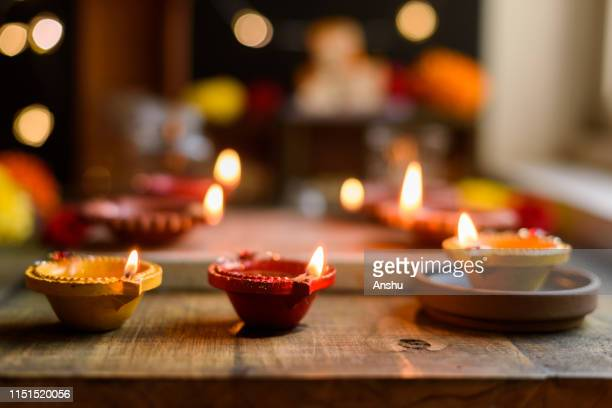 diwali celebrations with traditional clay oil diyas or lamps on wooden background with flower arrangement and fire crackers - diya oil lamp stock pictures, royalty-free photos & images