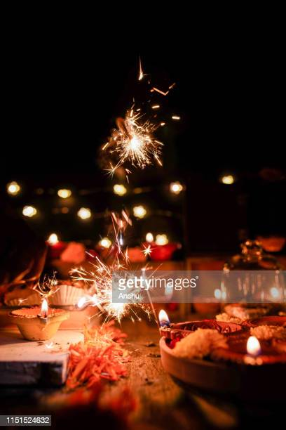 diwali celebrations with traditional clay oil diyas or lamps on wooden background with flower arrangement and fire crackers - diwali stock pictures, royalty-free photos & images