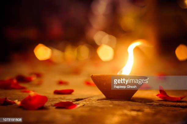 diwali lamps and rose petals - diwali stock pictures, royalty-free photos & images