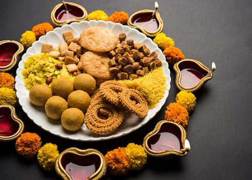 Diwali Rangoli or design made using Indian snacks/sweet and diya or lamp and flowers 1054227912