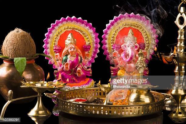 diwali thali in front of idols of lord ganesha and goddess lakshmi - goddess lakshmi stock photos and pictures