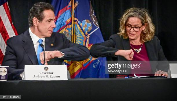 New York State Governor Andrew Cuomo elbow bumps Nassau County Executive Laura Curran to show a safe alternative to shaking hands during a press...