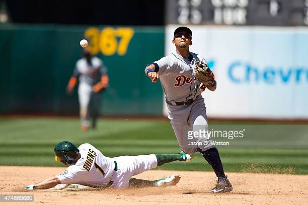 Dixon Machado of the Detroit Tigers completes a double play over Billy Burns of the Oakland Athletics during the sixth inning at Oco Coliseum on May...