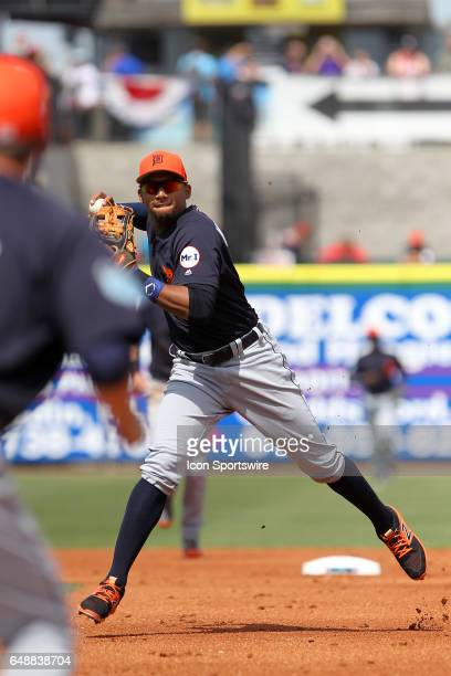 Dixon Machado of the Tigers sets up to throw the ball to first base for the out during the spring training game between the Detroit Tigers and the...