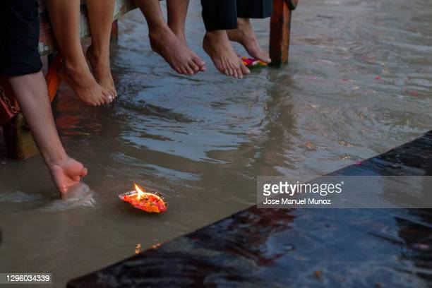 diya floating over river ganges - foot worship stock pictures, royalty-free photos & images