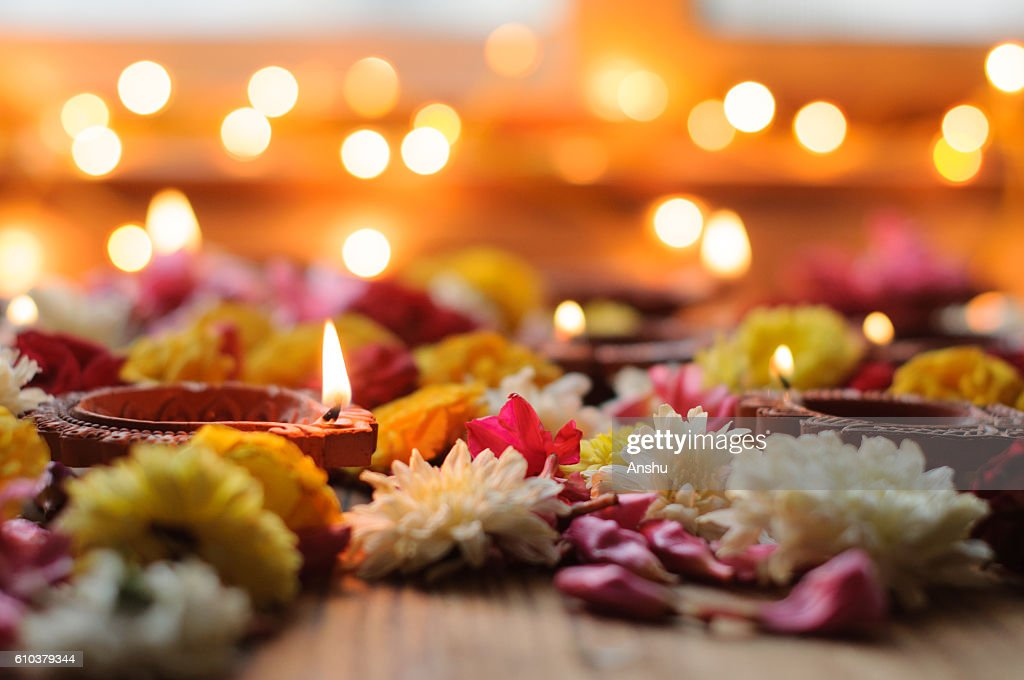 diya lamps lit during diwali celebration with flowers and sweets in background : Stock Photo