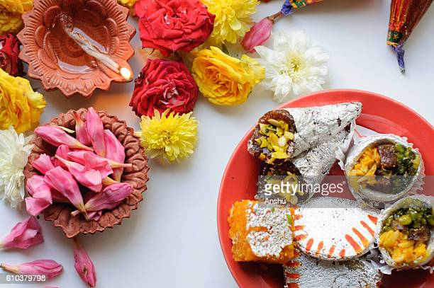 diya lamps lit during diwali celebration with flowers and sweets in background - diwali sweets stock photos and pictures