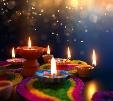 Diya lamps lit on colorful rangoli during diwali celebration 969343090