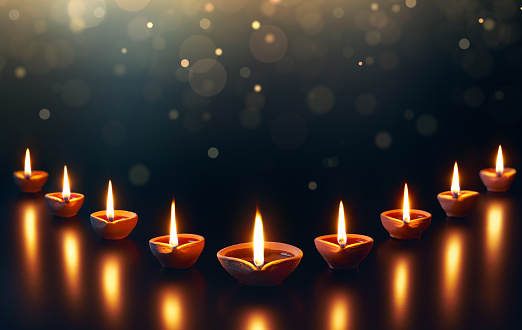 Diya lamps on a reflective base with glittering bokeh 995955626