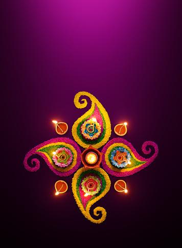 Diya oil lamps lit on colorful rangoli 985480770