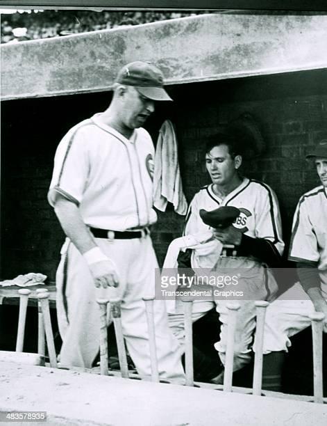 Dizzy Dean sweats on the dugout bench as manager Gabby Hartnett walks by in 1939 in Wrigley Field in Chicago Illinois