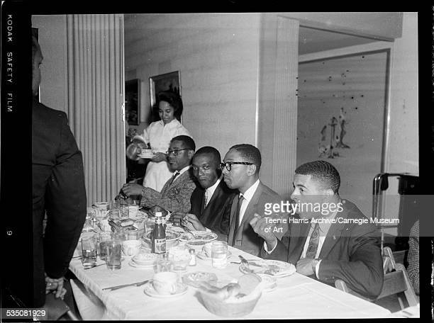 Dizzy Gillespie Walt Harper Billy Taylor and another man seated at banquet table eating with woman serving coffee in background Pittsburgh...