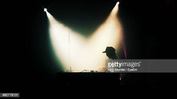 Dj Mixing Music In Darkroom At Nightclub