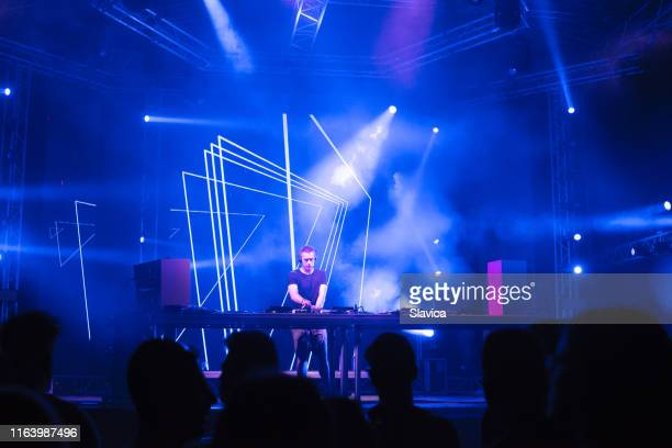 dj playing techno music on the stage - club dj stock pictures, royalty-free photos & images