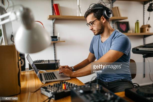 dj using laptop at home recording studio - post-production stock pictures, royalty-free photos & images