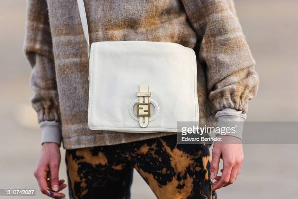 Djebril Irid @mingodebergamo wears a gray and beige checked wool pullover, a Fendi white bag, black and brown denim pants with printed patterns,...
