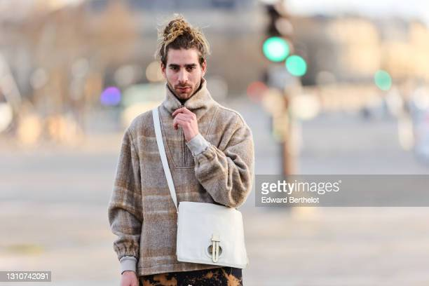 Djebril Irid @mingodebergamo wears a gray and beige checked wool pullover with turtleneck and front zipper, a Fendi white bag, during a street style...
