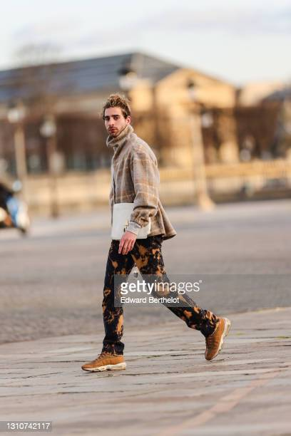 Djebril Irid @mingodebergamo wears a gray and beige checked wool pullover with turtleneck and front zipper, a Fendi white bag, black and brown denim...