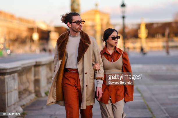 Djebril Irid @mingodebergamo wears sunglasses, a gray pullover, a beige trench coat with brown fluffy lapels, a chain belt, orange pants ; Alessandra...