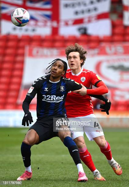 Djed Spence of Middlesbrough is put under pressure by Callum Styles of Barnsley FC during the Sky Bet Championship match between Barnsley and...