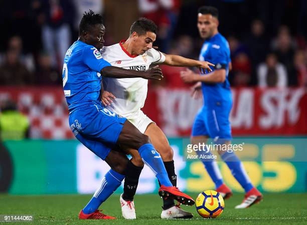 Djene Dakonamof Getafe CF competes for the ball with Wissam Ben Yedder of Sevilla FC during the La Liga match between Sevilla and Getafe at Estadio...