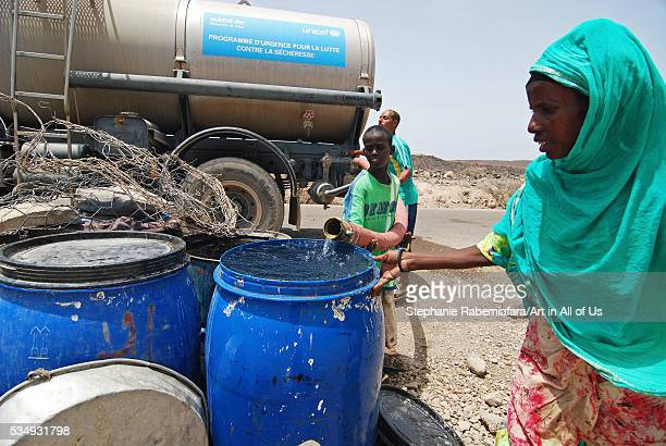 Djibouti Kharta teenager boy taking water from water containter truck provided by the Unicef in the desert