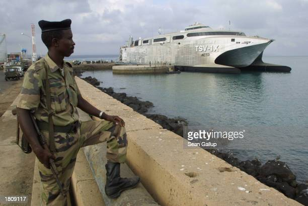 Djiboutian soldier stands guard near the USAV Spearhead an American experimental highspeed troop transporter February 22 2003 at the port at Djibouti...