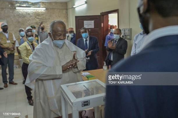 Djibouti's incumbent president Ismail Omar Guelleh clasps his hands after he cast his ballot as his officials applaud at the Ras-Dika district...