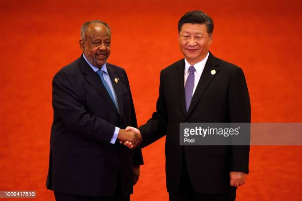Djibouti's President Ismail Omar Guelleh left shakes hands with Chinese President Xi Jinping as they pose for photograph during the Forum on...