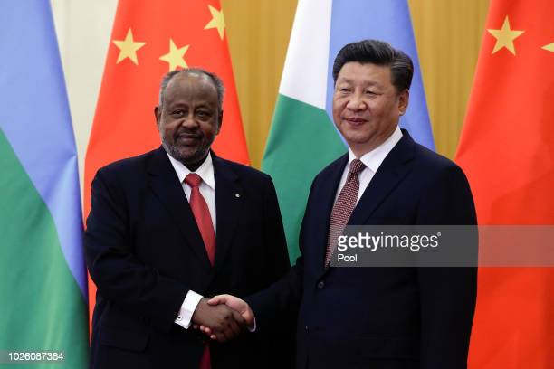 Djibouti's President Ismail Omar Guelleh shakes hands with Chinese President Xi Jinping before their bilateral meeting at the Great Hall of the...