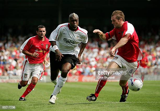 Djibril Cisse of Liverpool attempts to move past Shaun Pejic of Wrexham during the preseason friendly match between Wrexham and Liverpool at The...