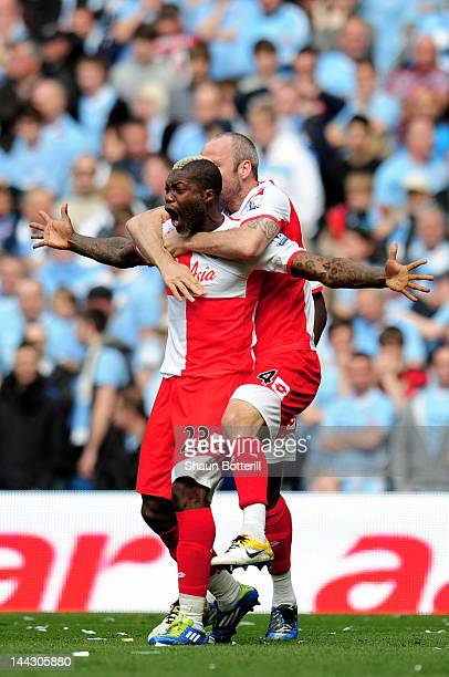 Djibril Cisse of QPR celebrates with teammate Shaun Derry after scoring his team's first goal during the Barclays Premier League match between...