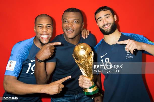 Djibril Sidibé and Nabil Fekir of France pose with Marcel Desailly and the Champions World Cup trophy after the 2018 FIFA World Cup Russia Final...