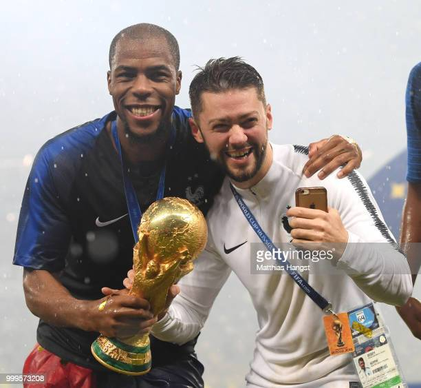Djibril Sidibe of France and Arnaud Berry celebrate victory with the World Cup trophy during the 2018 FIFA World Cup Final between France and Croatia...