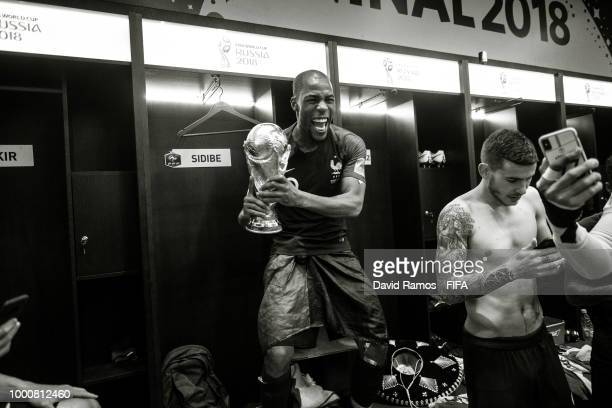 Djibril Sidibe of France celebrates in the dressing room whit the World Cup Trophy in the France's dressing room following his side victory in the...