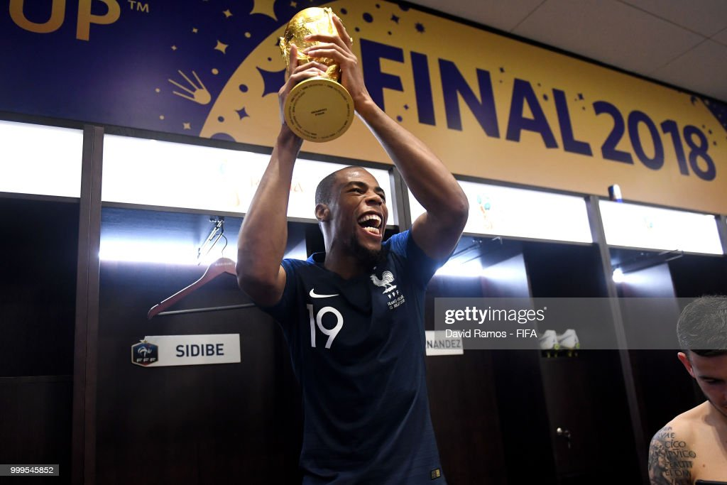 Djibril Sidibe of France celebrates with the World Cup Trophy in the dressing room following his sides victory in the 2018 FIFA World Cup Final between France and Croatia at Luzhniki Stadium on July 15, 2018 in Moscow, Russia.
