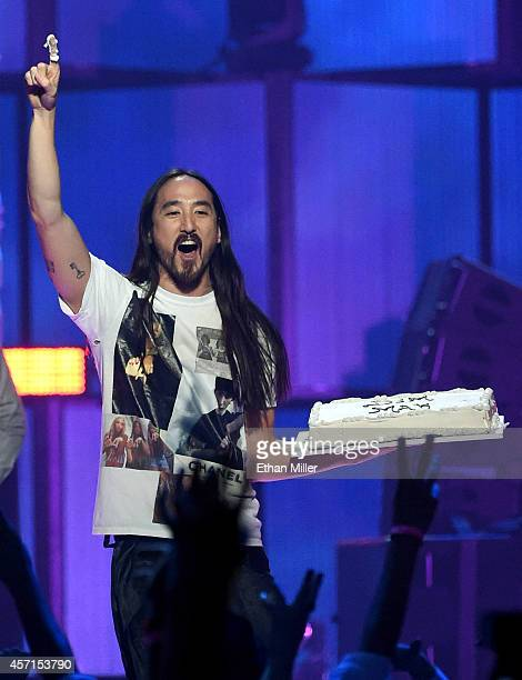 DJ/producer Steve Aoki carries a cake as he performs during the 2014 iHeartRadio Music Festival at the MGM Grand Garden Arena on September 19 2014 in...