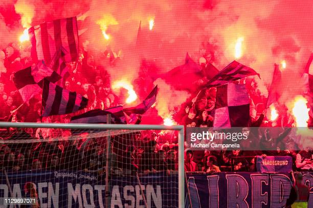Djurgarden supporters wave light flares during a quarter-final match in the Swedish Cup between Djurgardens IF and Hammarby IF at Tele2 Arena on...