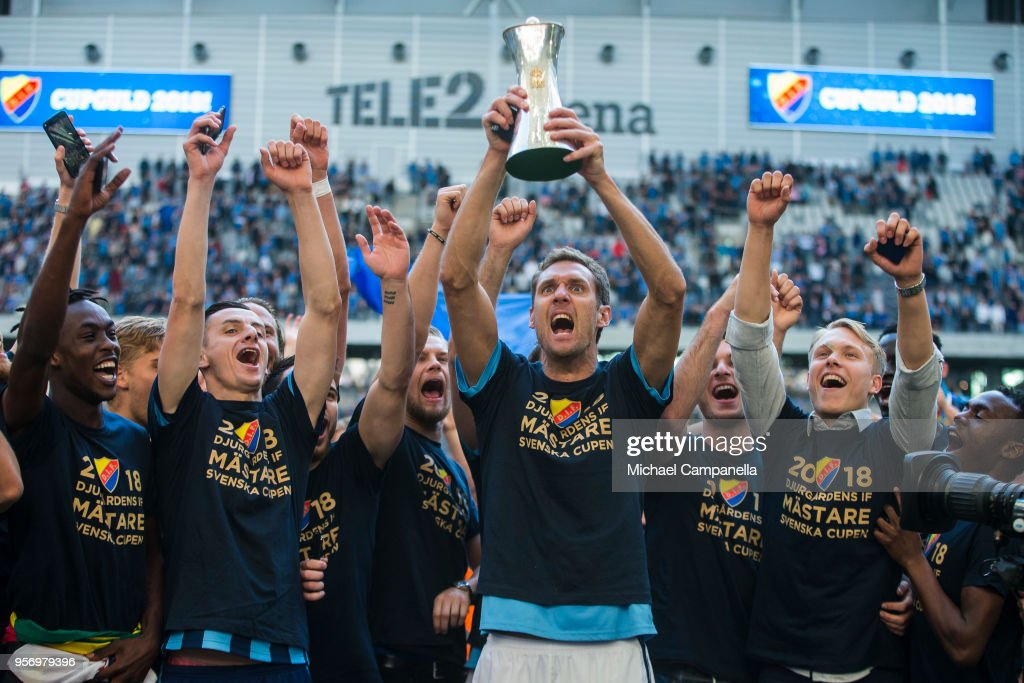 Djurgardens IF goalkeeper Andreas Isaksson raises the Swedish Cup as his teammates celebrate winning the Svenska Cupen Final between Djurgardens IF and Malmo FF at Tele2 Arena on May 10, 2018 in Stockholm, Sweden.