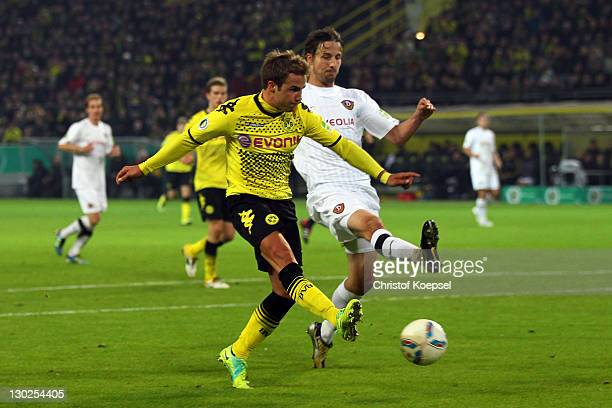 dMario Goetze of Dortmund scores the second goal against Martin Stoll of Dresden during the second round DFB Cup match between Borussia Dortmund and...