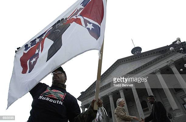 Dmitri Ford of Charleston SC joins protestors January 21 2002 at the steps of the statehouse in Columbia SC to call for the removal of the...