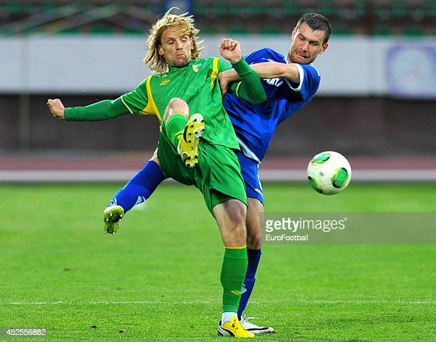 Dmitri Kavalyonok of FC Neman Grodno is tackled by Andrei Zalesky of FC Dinamo Minsk during the Belarusian Premier League match between FC Neman...