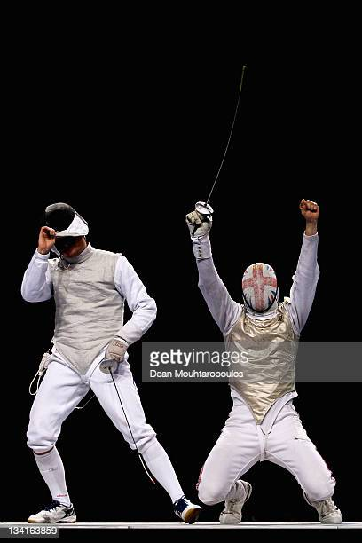 Dmitri Rigine of Russia looks dejected as Richard Kruse celebrates winning the gold medal win in the Men's Foil Team Final at the Fencing...
