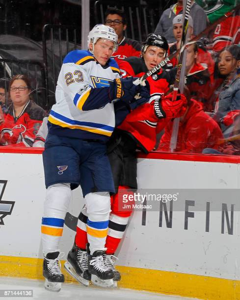 Dmitrij Jaskin of the St Louis Blues checks John Moore of the New Jersey Devils during the first period on November 7 2017 at Prudential Center in...