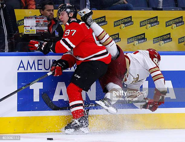Dmitry Buynitskiy of the Quebec Remparts hits Antoine Morand of the Acadie-Bathurst Titan during their QMJHL hockey game at the Centre Videotron on...