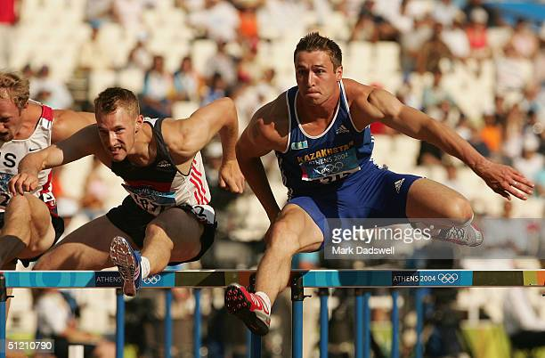 Dmitry Karpov of Kazakhstan and Stefan Drews of Germany compete in the 110 metre hurdle discipline of the men's decathlon on August 24, 2004 during...