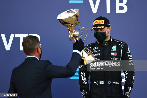 Dmitry Kozak Deputy Chief of Staff of the Presidential Executive Office presents Valtteri Bottas of Finland and Mercedes GP with his winners trophy...