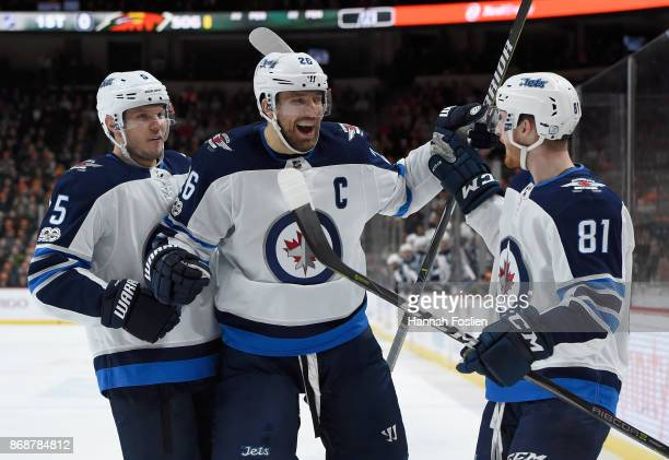 Dmitry Kulikov and Blake Wheeler of the Winnipeg Jets congratulate teammate Kyle Connor on scoring a goal against the Minnesota Wild during the first...