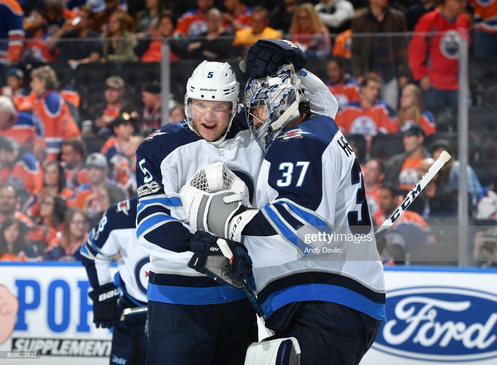 Dmitry Kulikov #5 and Connor Hellebuyck #37 of the Winnipeg Jets celebrate after winning the game against the Edmonton Oilers on October 9, 2017 at Rogers Place in Edmonton, Alberta, Canada.